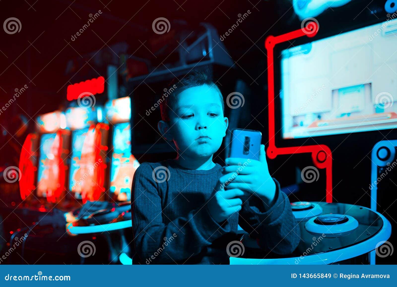 Chłopiec w gemowym centrum ono strzela na wideo na telefonie Neonowy oświetlenie Chłopiec blogger