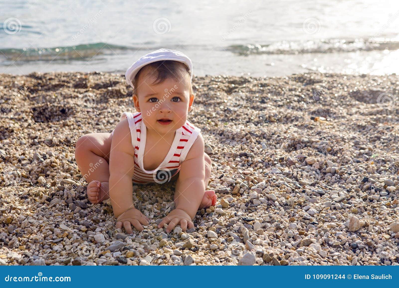 Chłopiec w kapeluszu na plażowych otoczakach