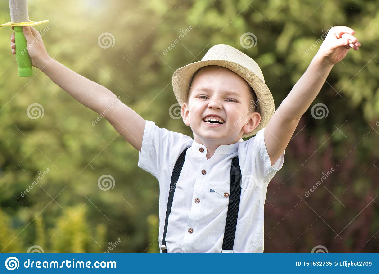 Chłopiec w słomianego kapeluszu sztukach w parku i spacerach