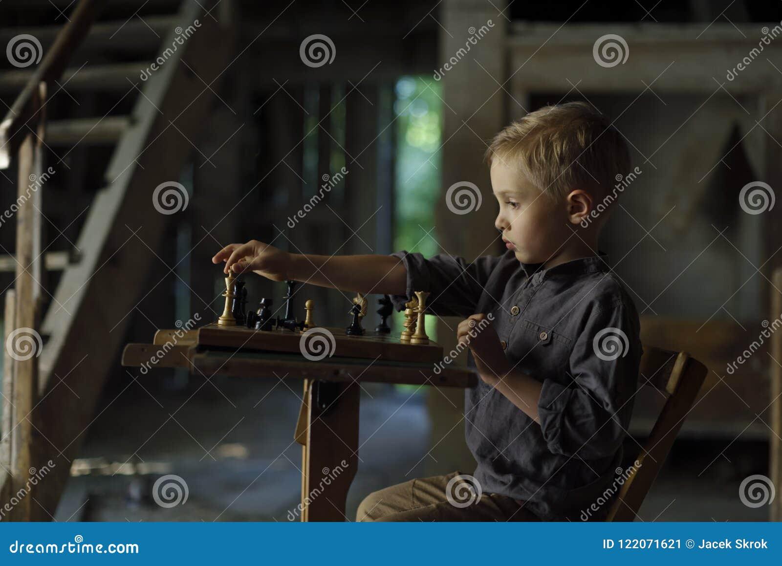 Chłopiec w starym domu bawić się szachy