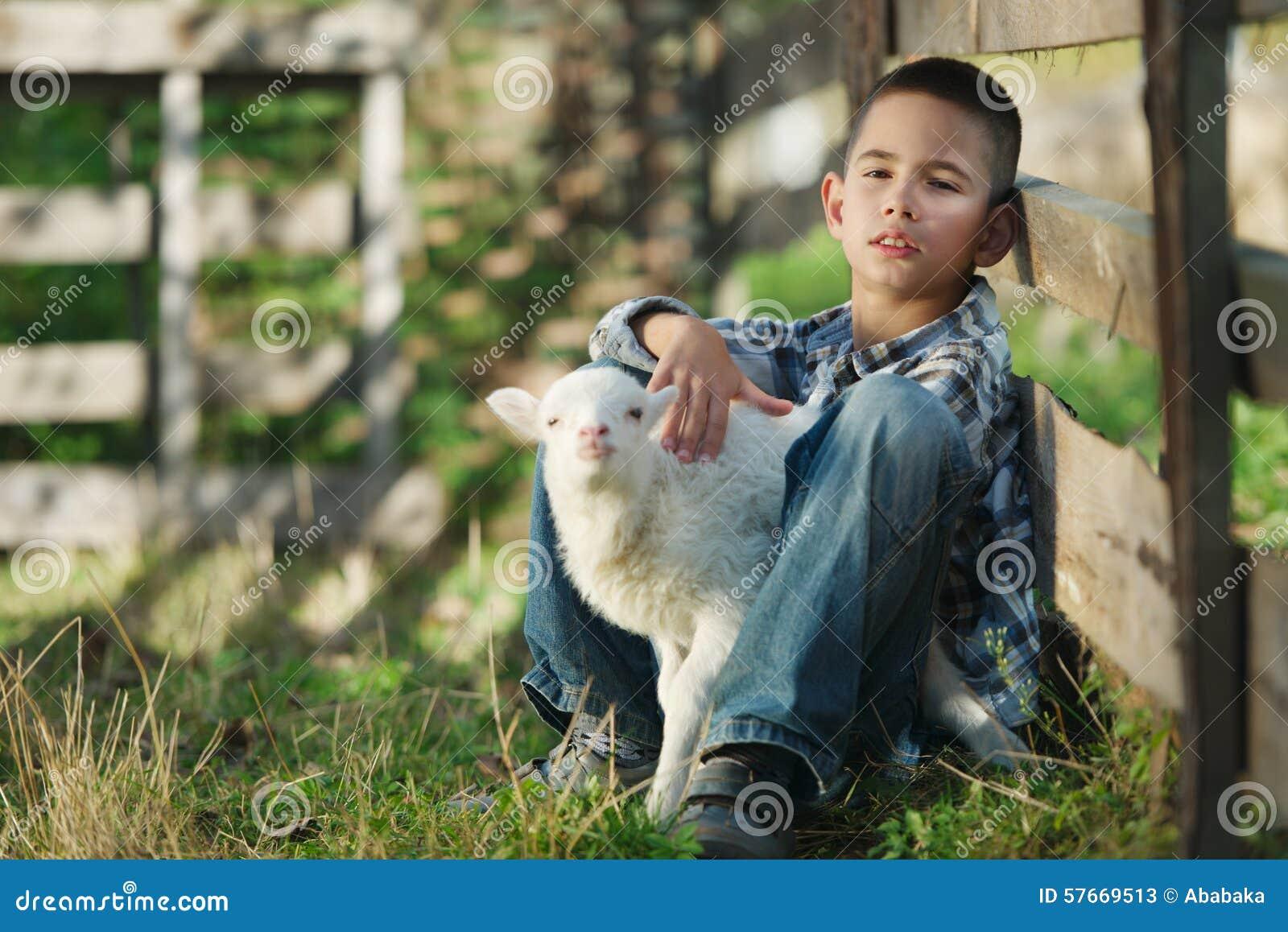 Chłopiec z barankiem na gospodarstwie rolnym