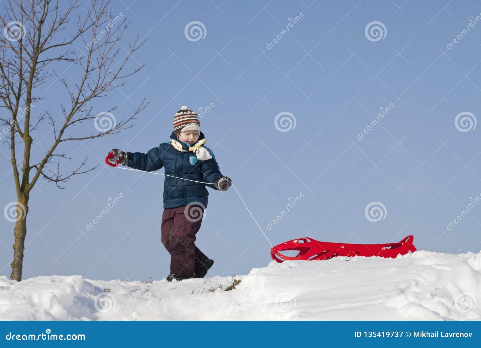 Chłopiec z czerwonym klingerytu saneczki na śnieżnym wzgórzu