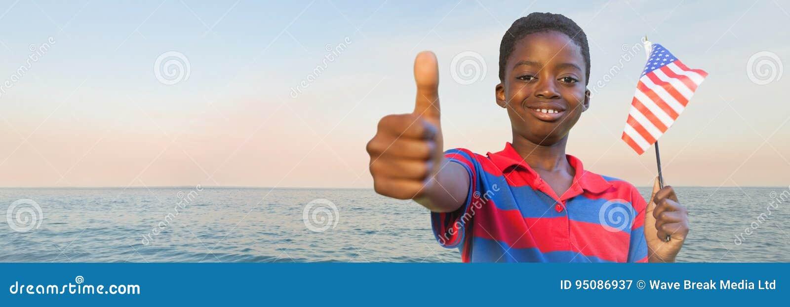 Chłopiec z flaga amerykańską daje aprobatom przeciw wodzie i evening niebo