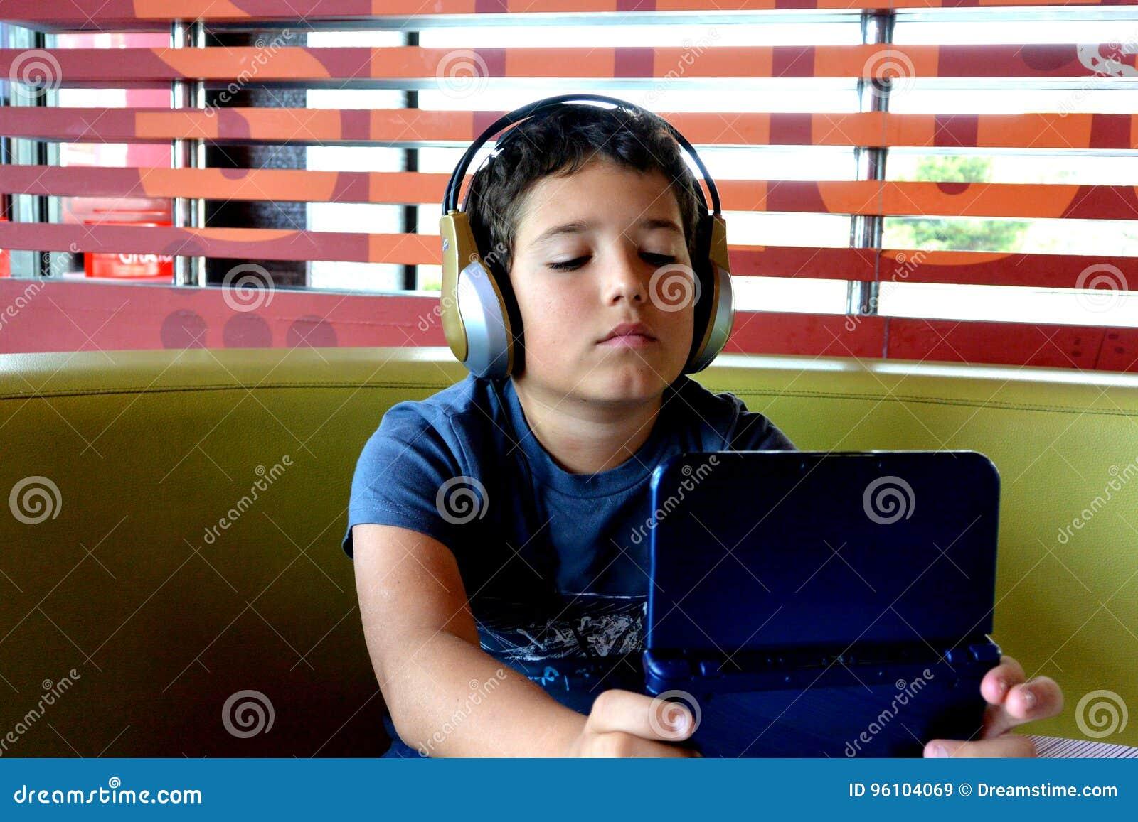 Chłopiec z hełmofonami bawić się z elektroniczną grze