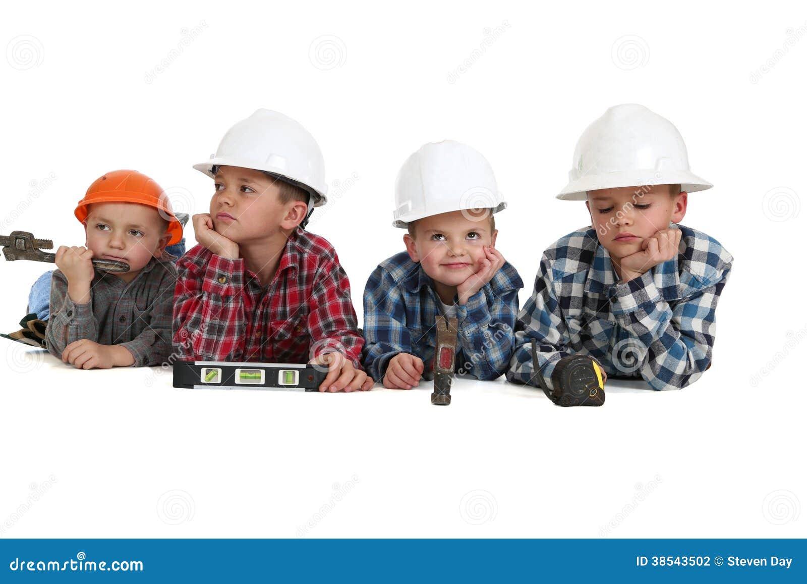 Chłopiec z narzędziami i hardhats na ich żołądkach