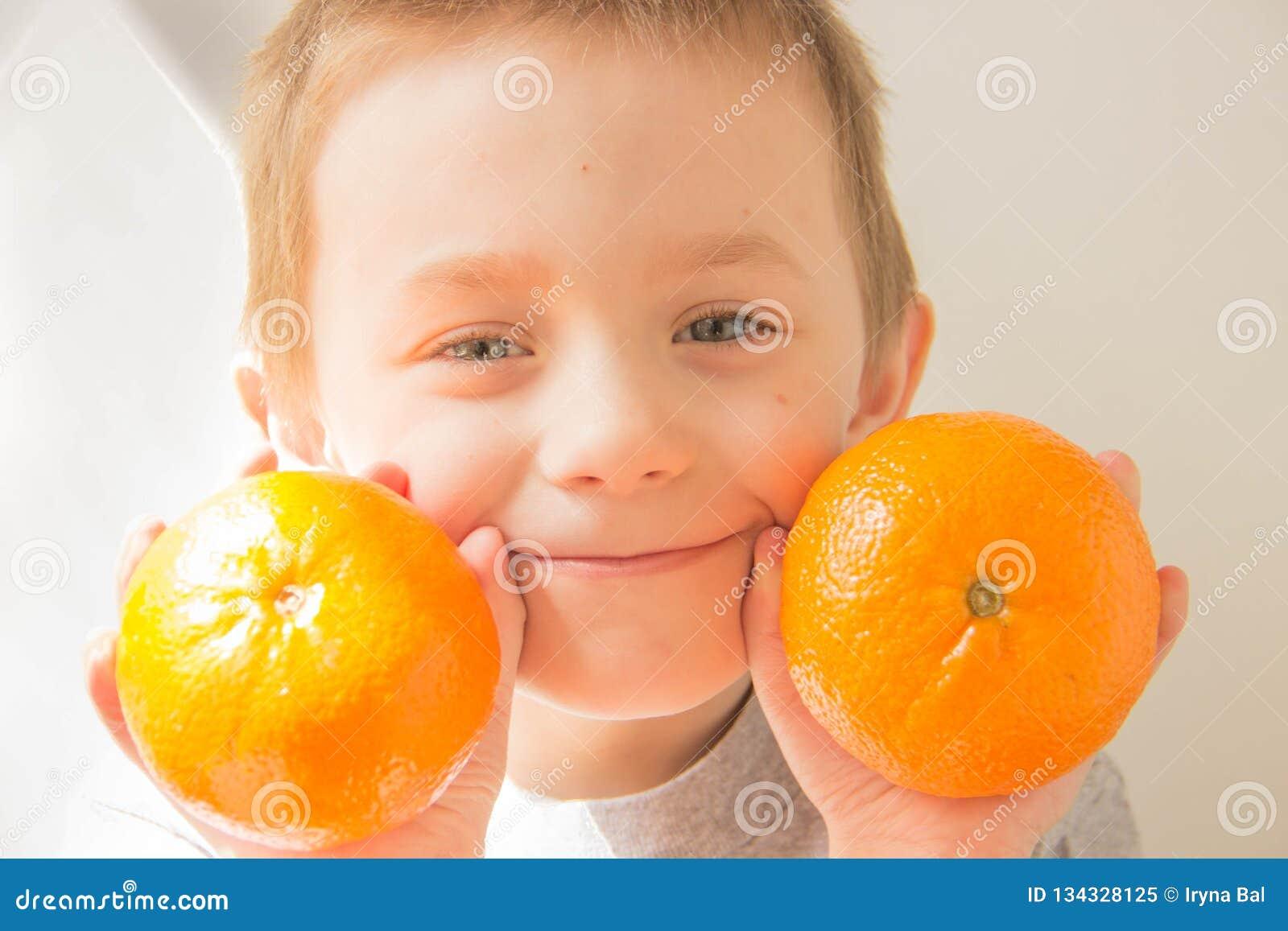 Chłopiec z pomarańczami w jego rękach