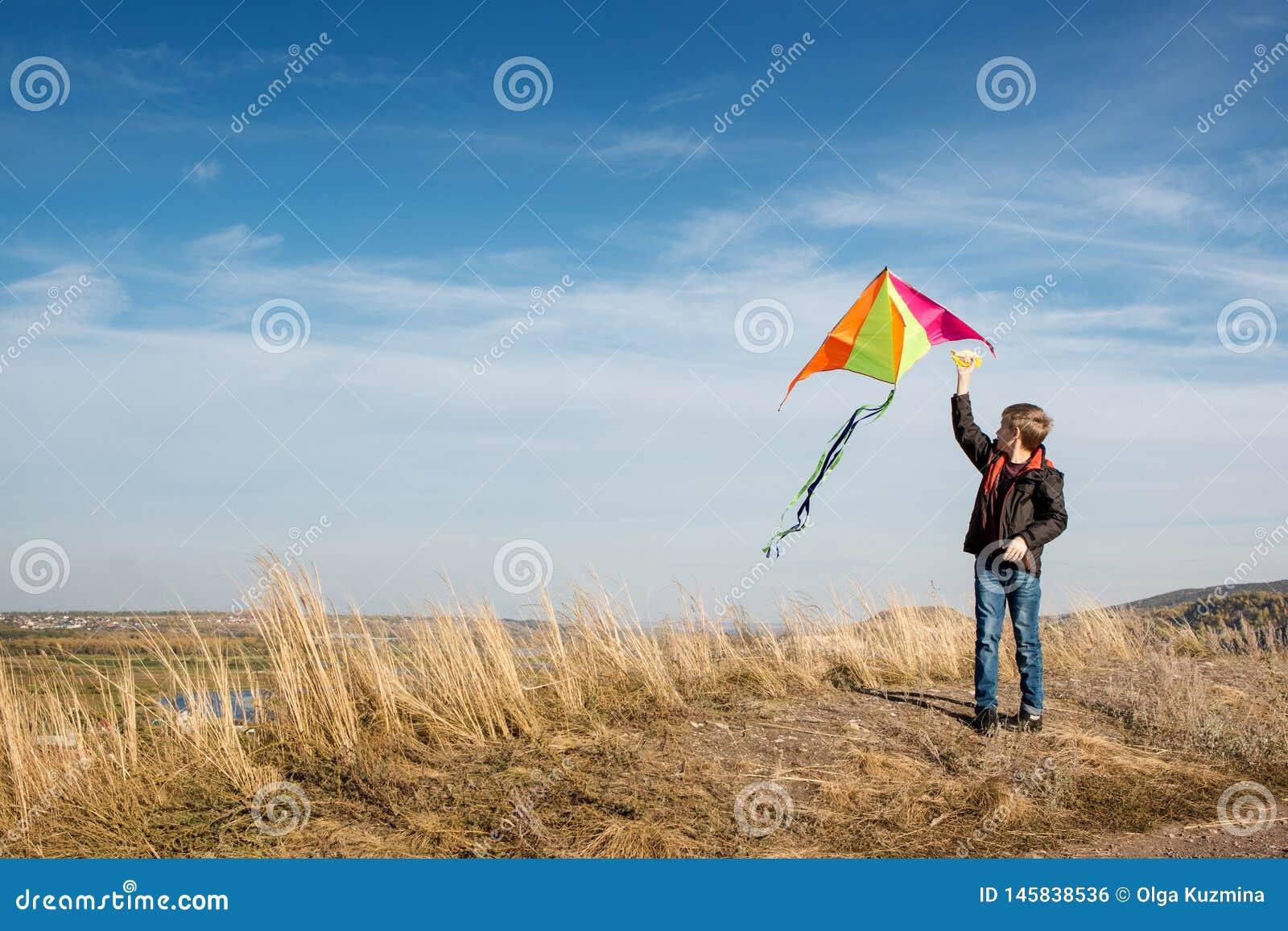 Ch?opiec z kani? przeciw niebieskiemu niebu jasny dzie? ?wieci s?o?ce Silny wiatr Ch?opiec Europejski pojawienie, ubieraj?ca w ca