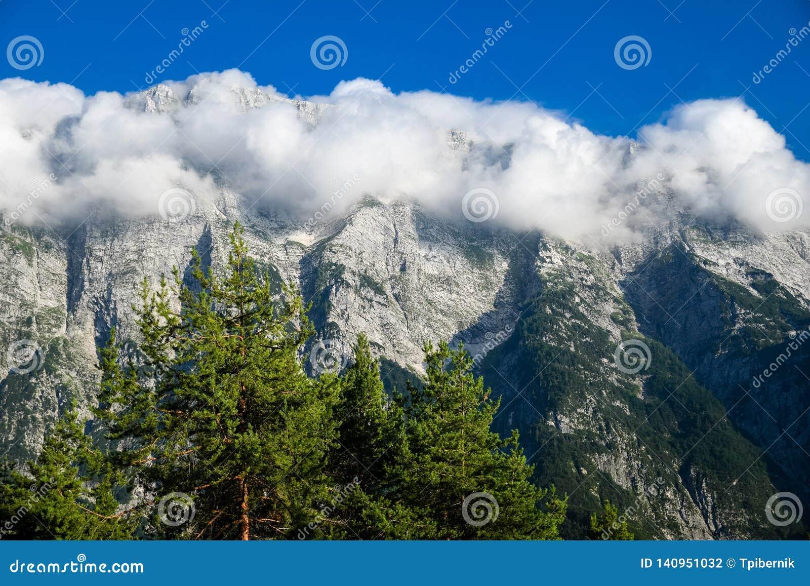 Chaîne de haute montagne avec des dessus couverts en nuages