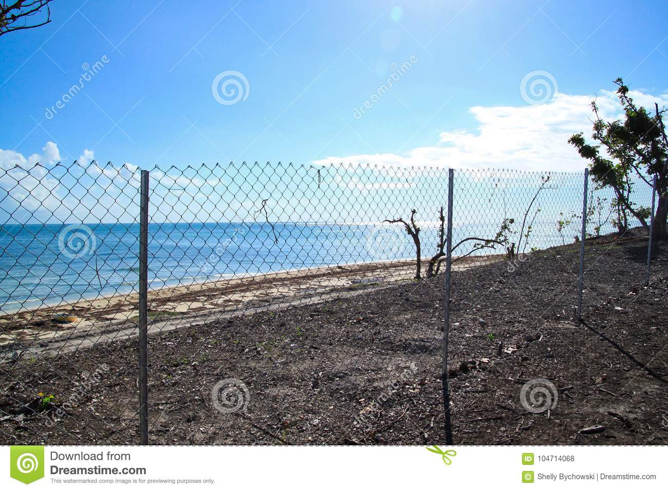 Chain link fence blocking off recovering area of beautiful Florida Keys beach after being destroyed by Hurricane Irma in 2017