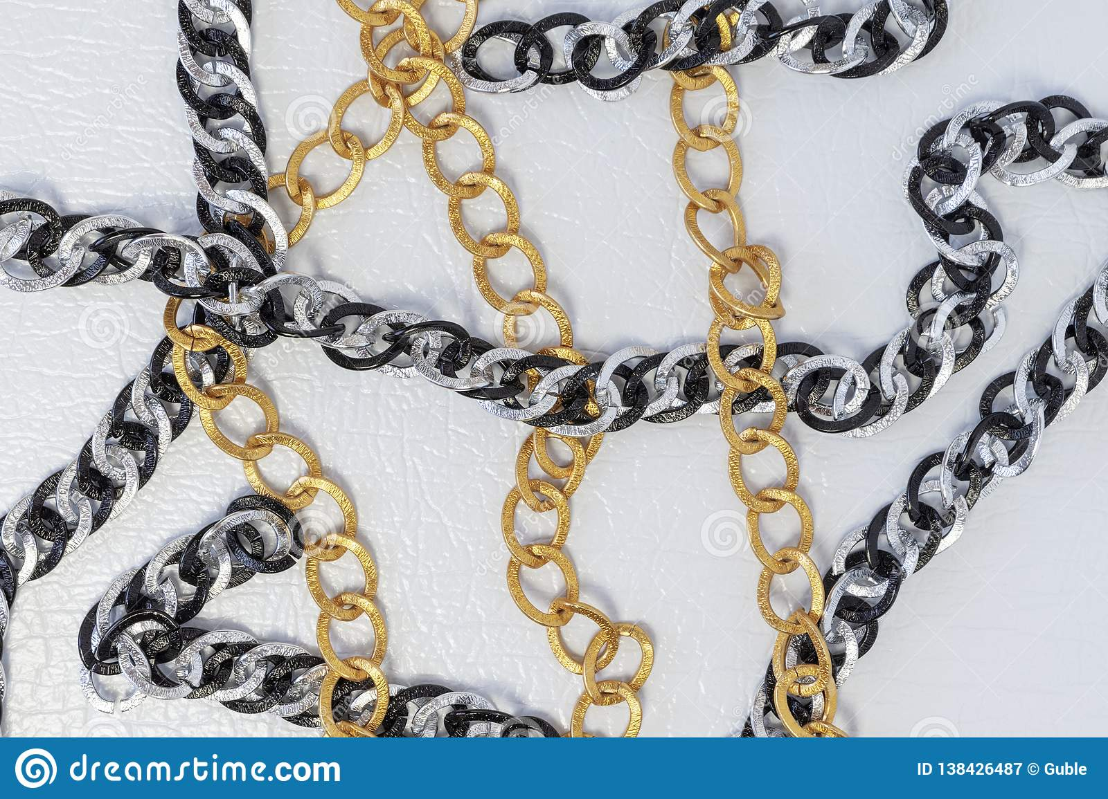 Chains on white leather background. Silver and gold color chains