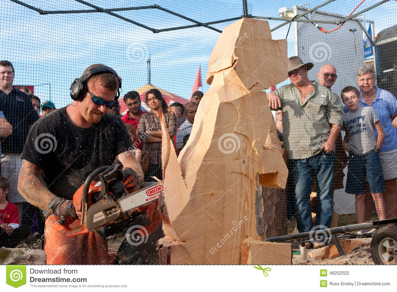 Chainsaw sculptor creates wooden dog sculpture editorial