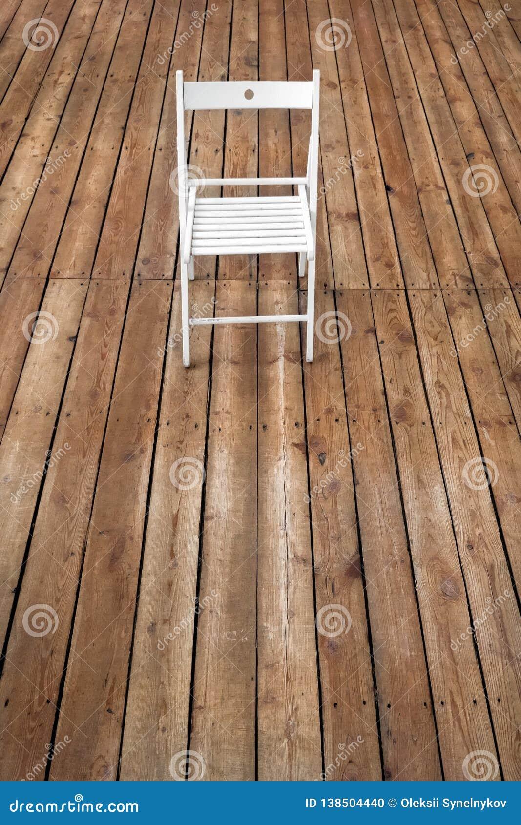 Chair and empty space on wooden floor. Single chair standing alone on wooden floor in empty room. Blank floor background. Studio