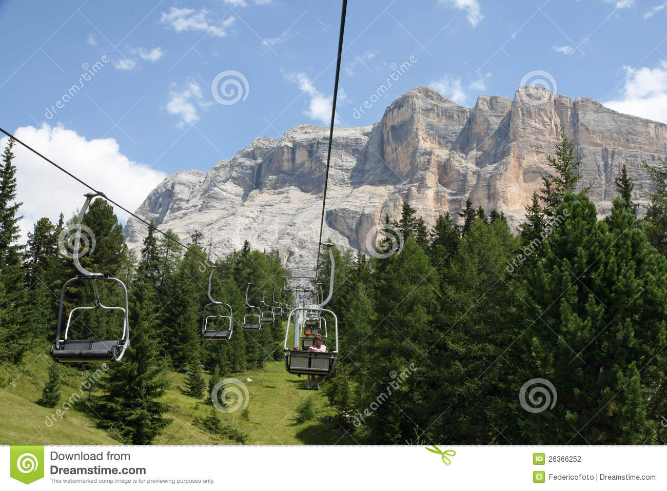 Chair lift people up towards the top of the Dolomites
