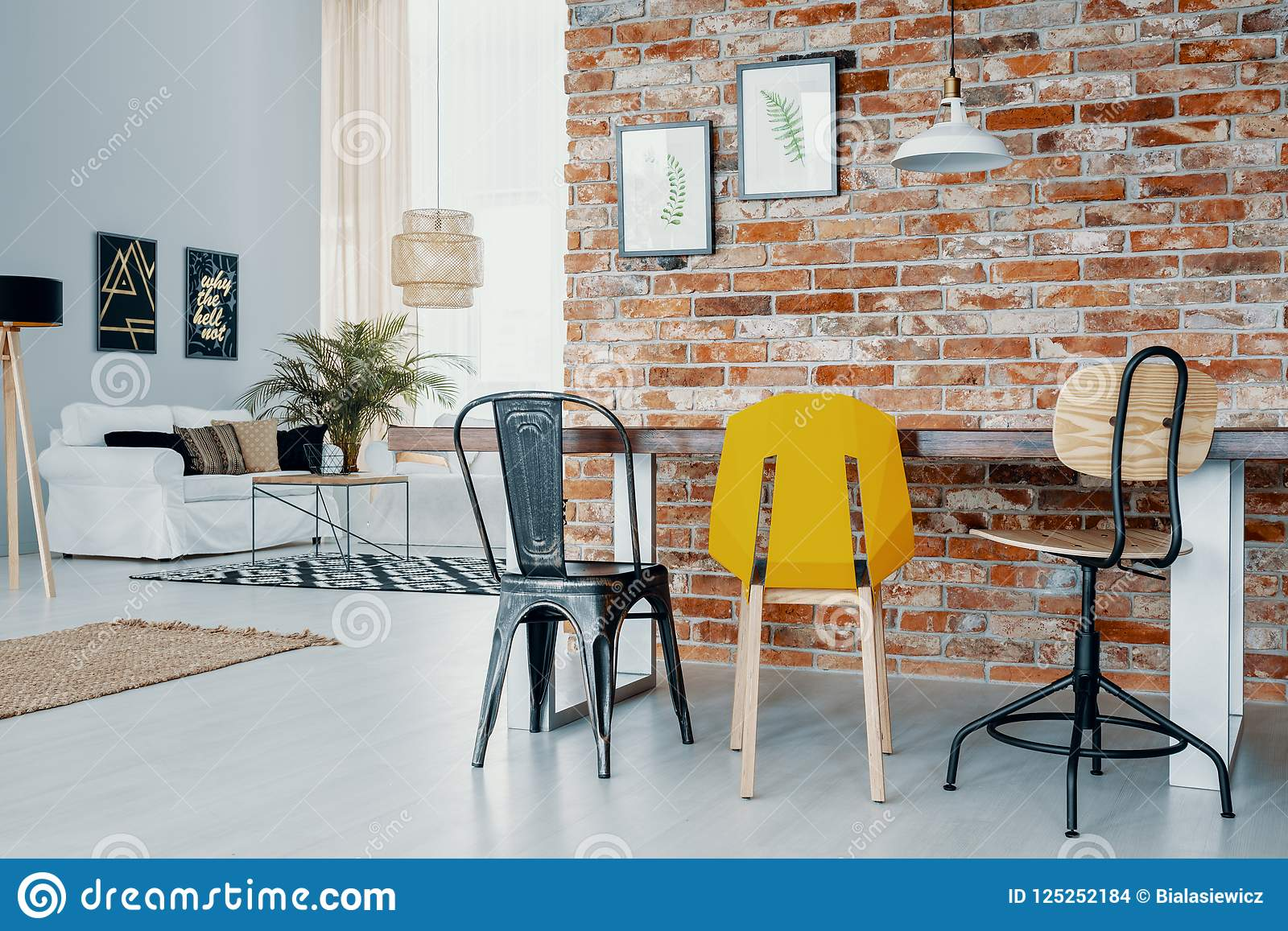 Chairs At Dining Table Against Red Brick Wall With Posters In Open Space Interior With White Sofa Real Photo Stock Photo Image Of Modern Furniture 125252184