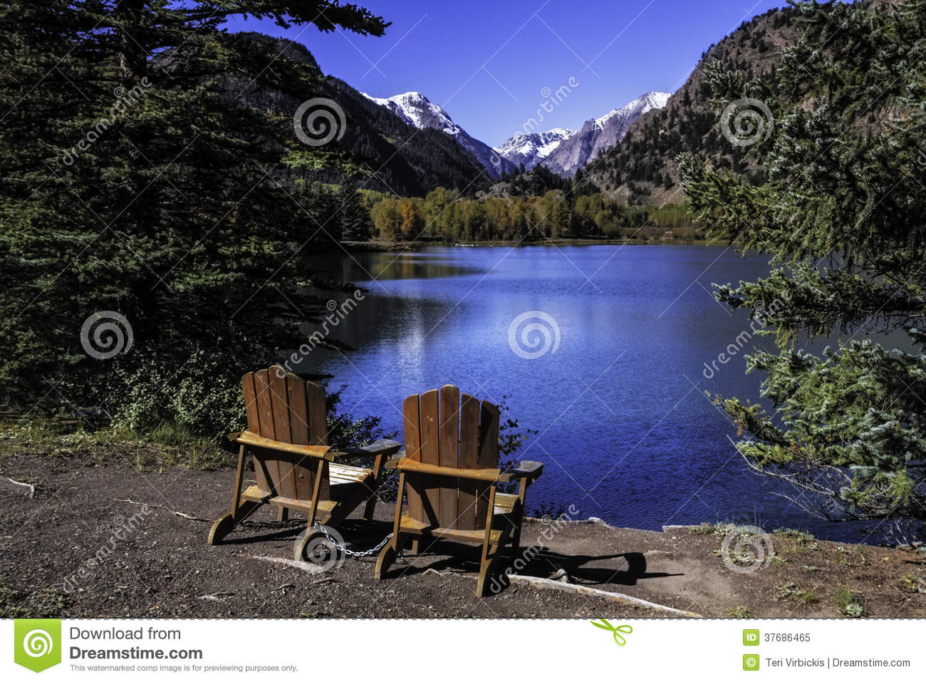 pair of adirondack chairs sitting by lake
