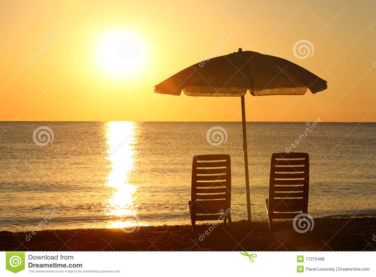 Chairs stand on beach under opened umbrella