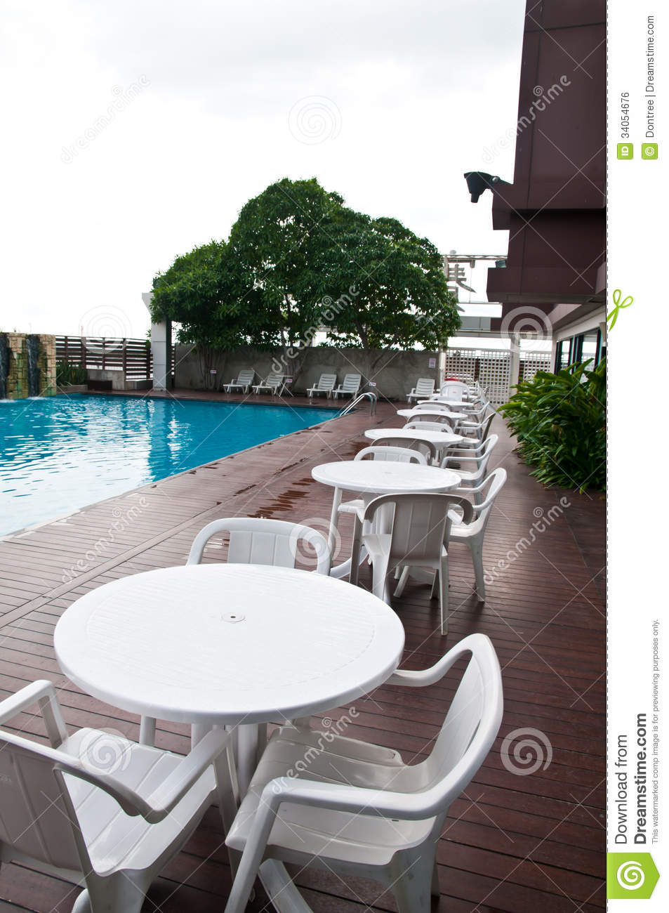 Table with chairs standing against the swimming pool & Chairs Standing Against The Swimming Pool Stock Photo - Image of ...