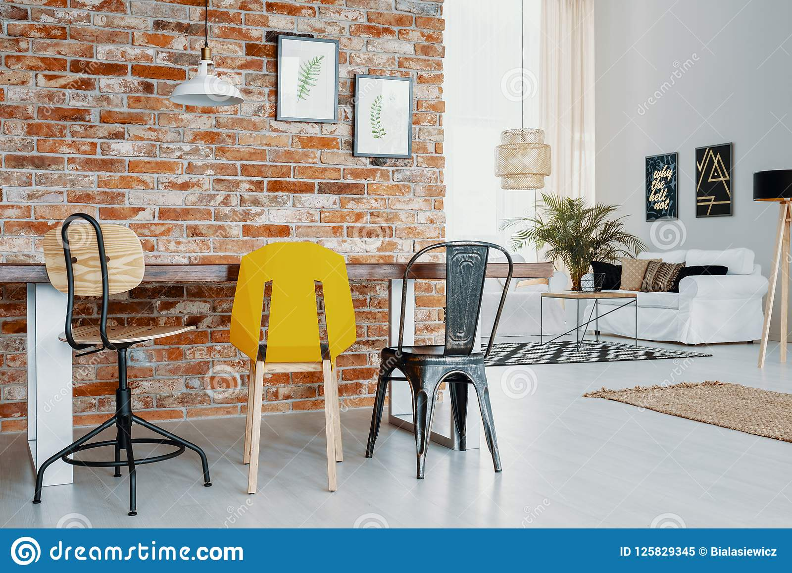 Red brick furniture Loft Chairs At Table Against Red Brick Wall With Posters In Modern Apartment Interior With Lamp Zebracolombiaco Chairs At Table Against Red Brick Wall With Posters In Modern