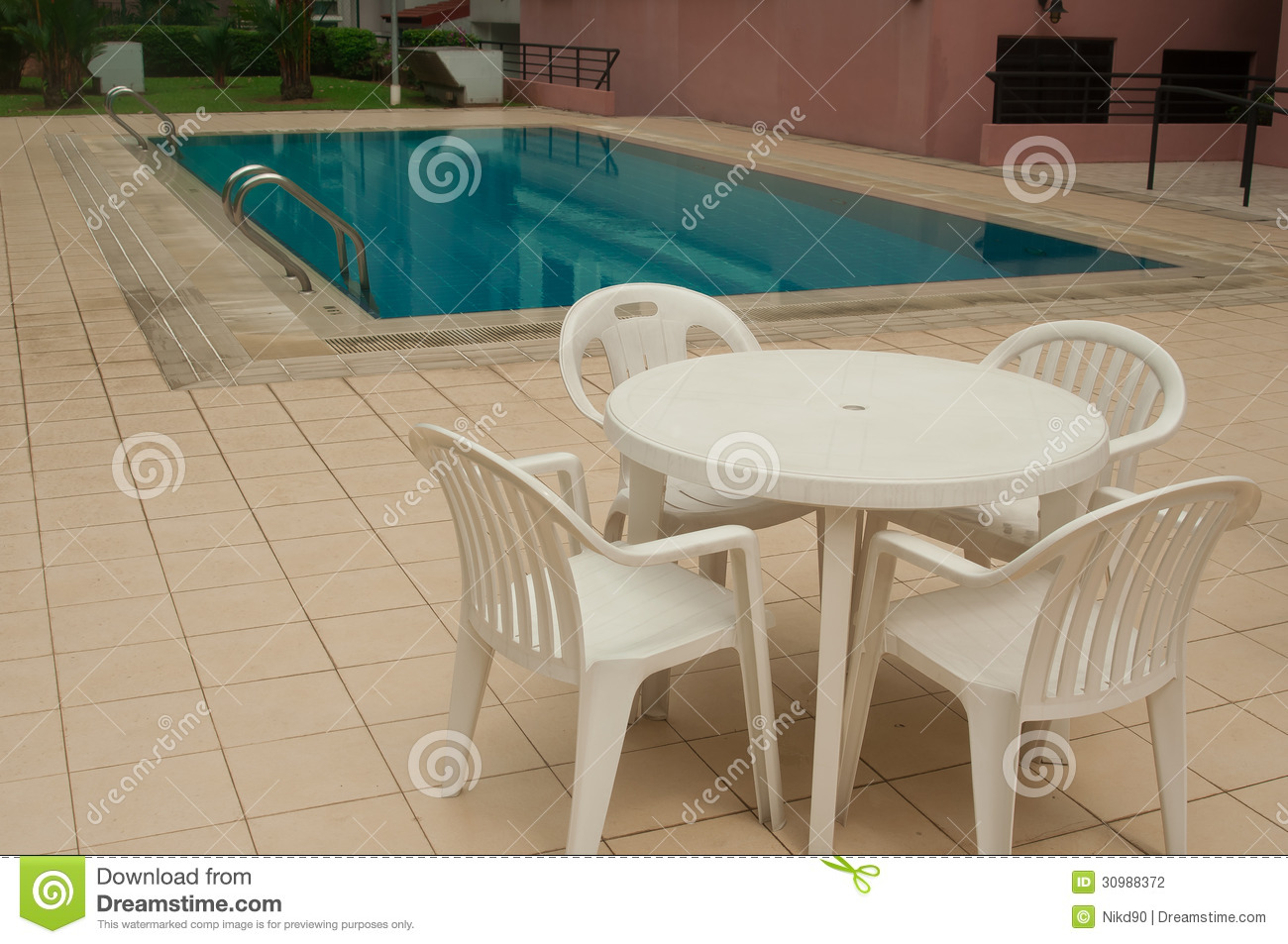 Chairs and table beside swimming pool inside the aparment for Poolside table and chairs