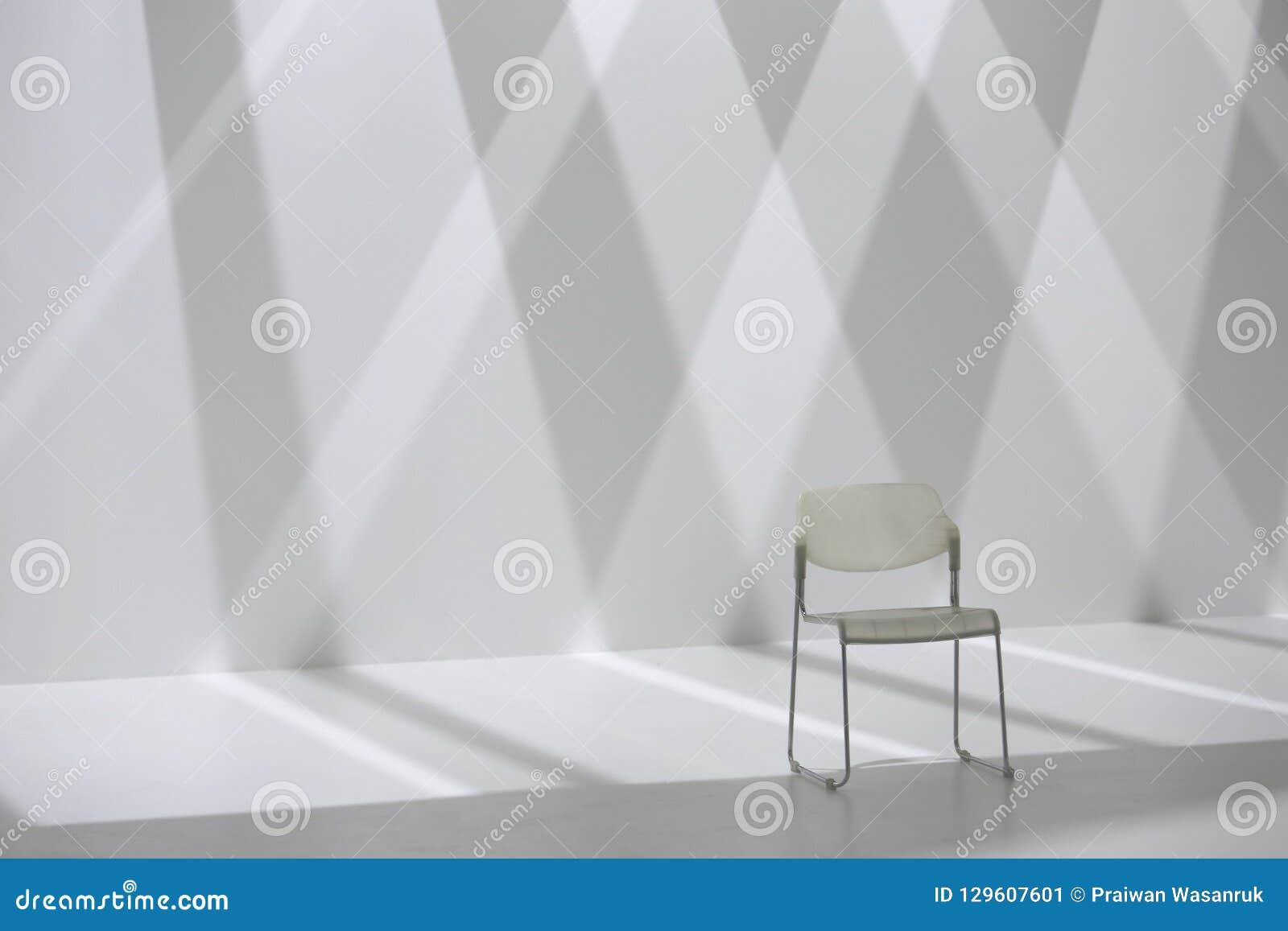 Chaise blanche devant le mur d ombre de forme de diamant