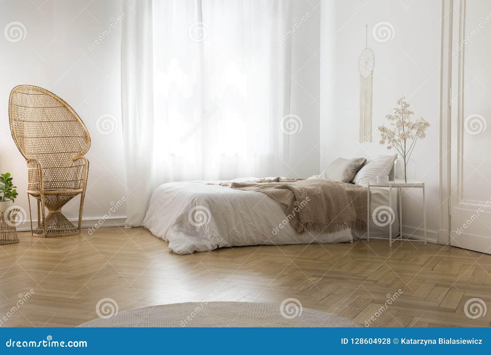 Chaise de paon de rotin à côté de fenêtre dans l intérieur blanc de chambre à coucher avec la couverture sur le lit