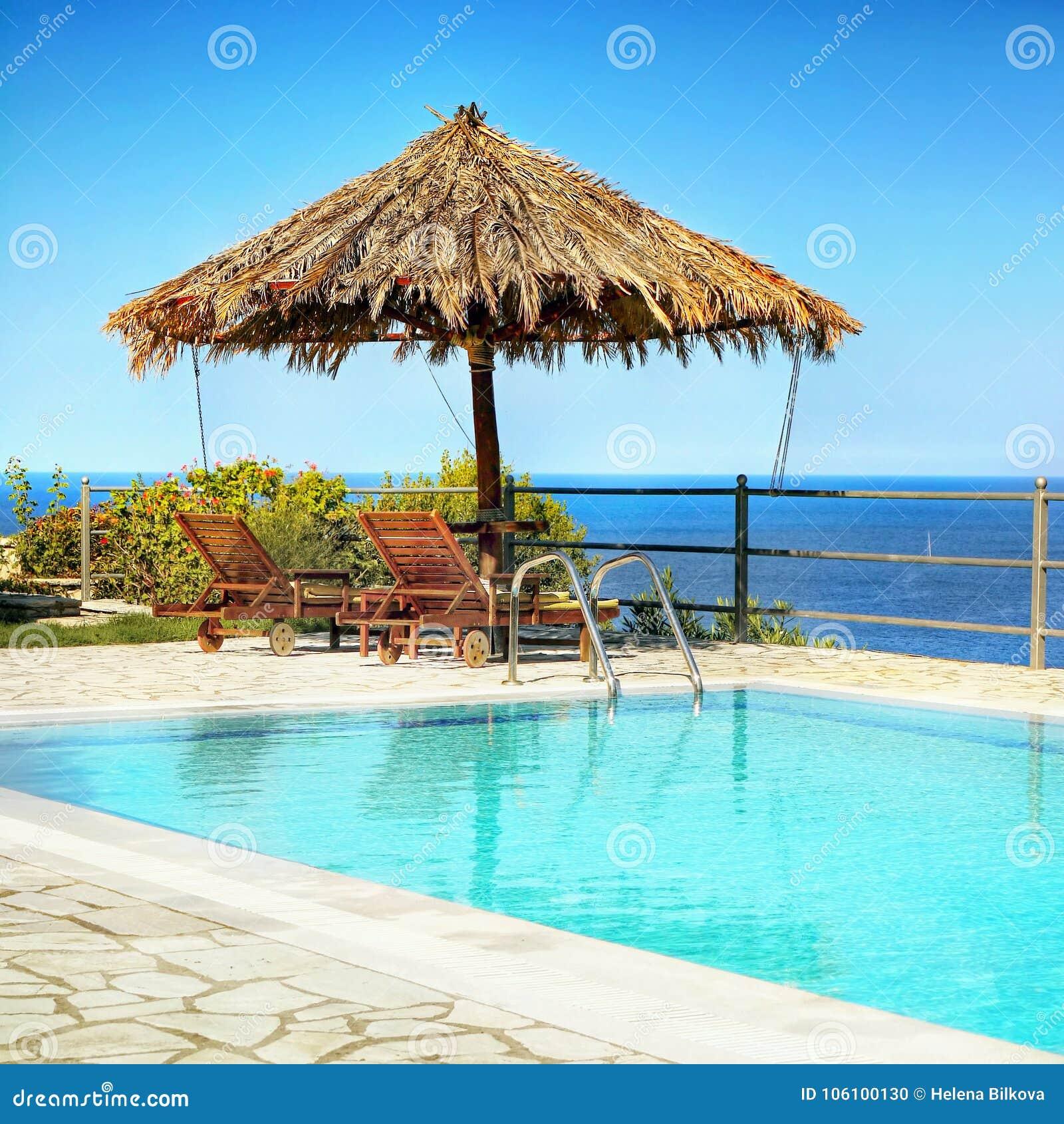 Chaise-lounge dell ombrello della piscina, vista del mare