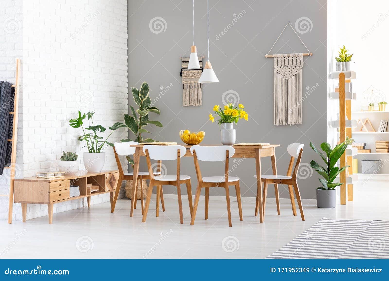 Beau Chaises Blanches à La Table En Bois Avec Les Fleurs Jaunes Dans Lu0027intérieur  De Salle à Manger Avec Des Usines Photo Réelle