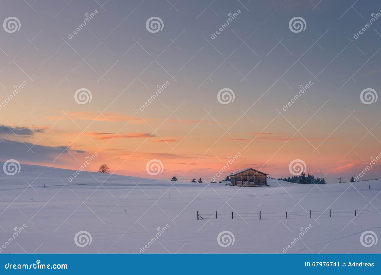 Chalé só no prado nevado no por do sol do inverno