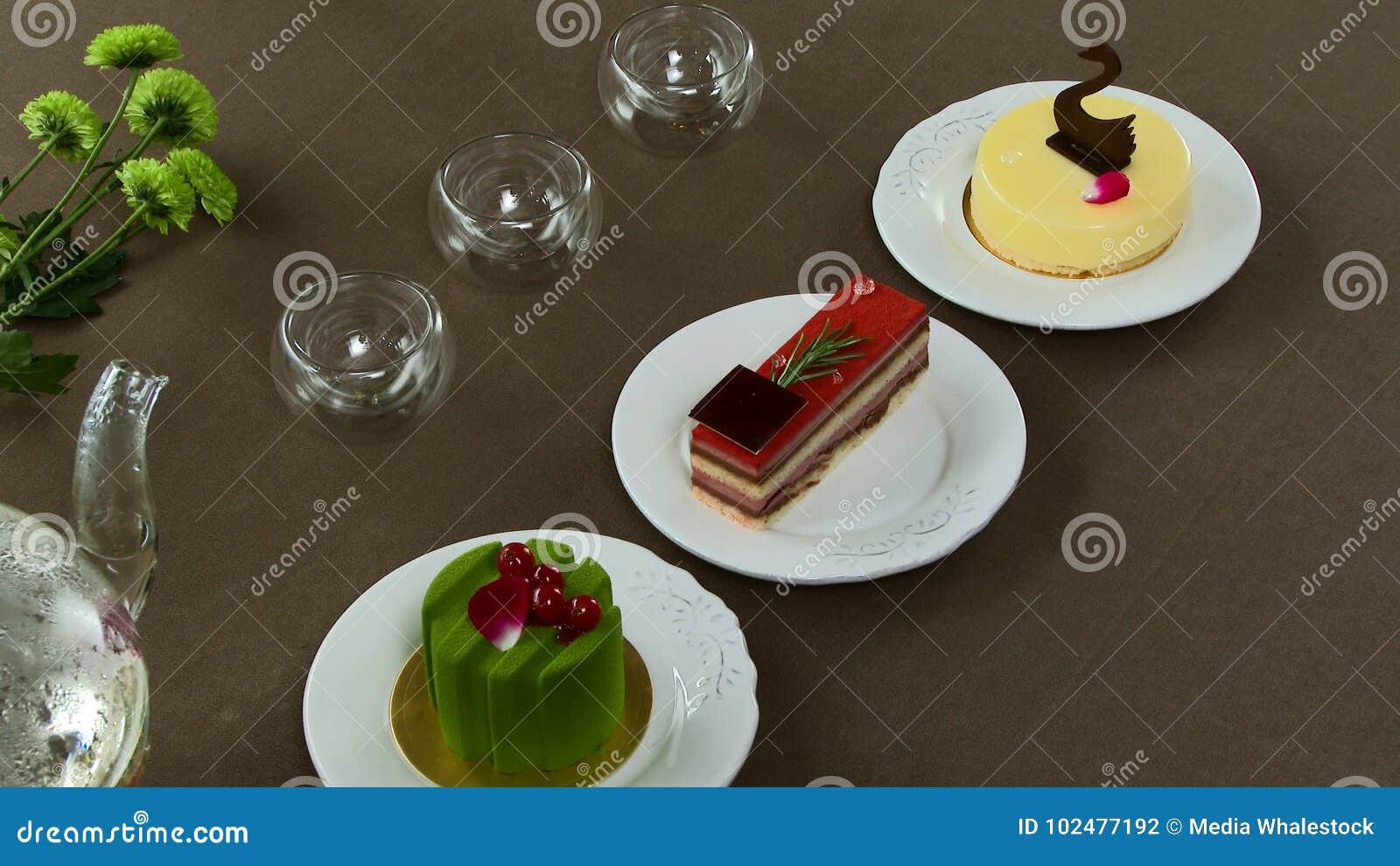 Chaleira transparente bonita do bule com chá preto verde saboroso com maçã, com velas e com a sobremesa no