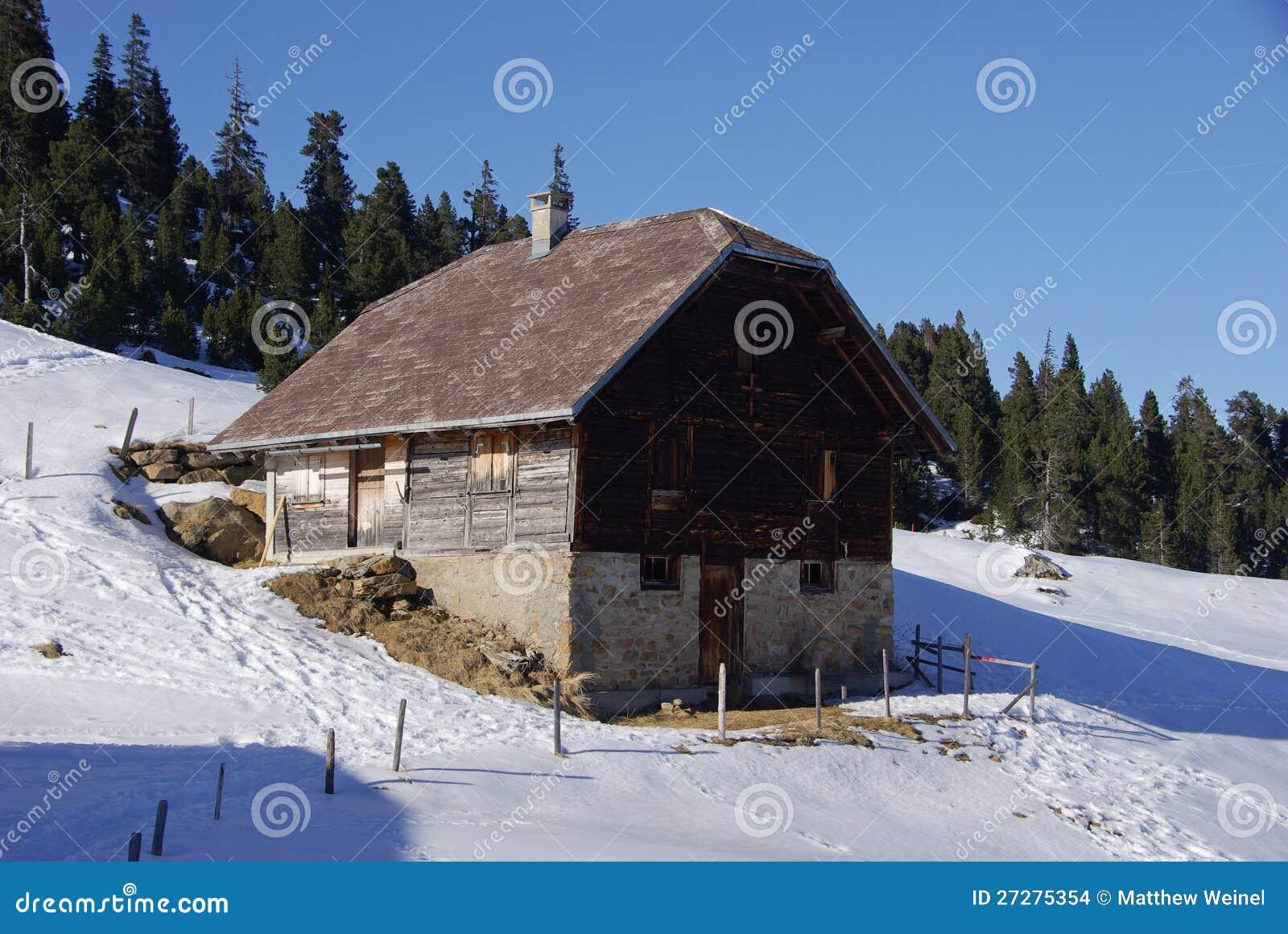 Chalet på den snöig bergssidan