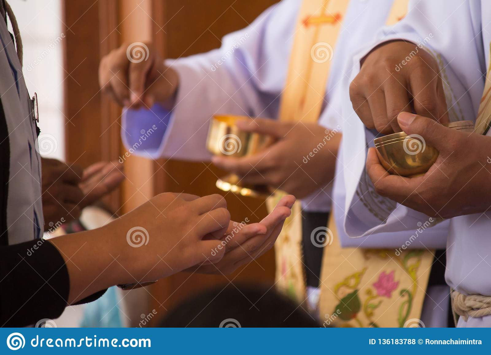 The chalice and the priest`s hand