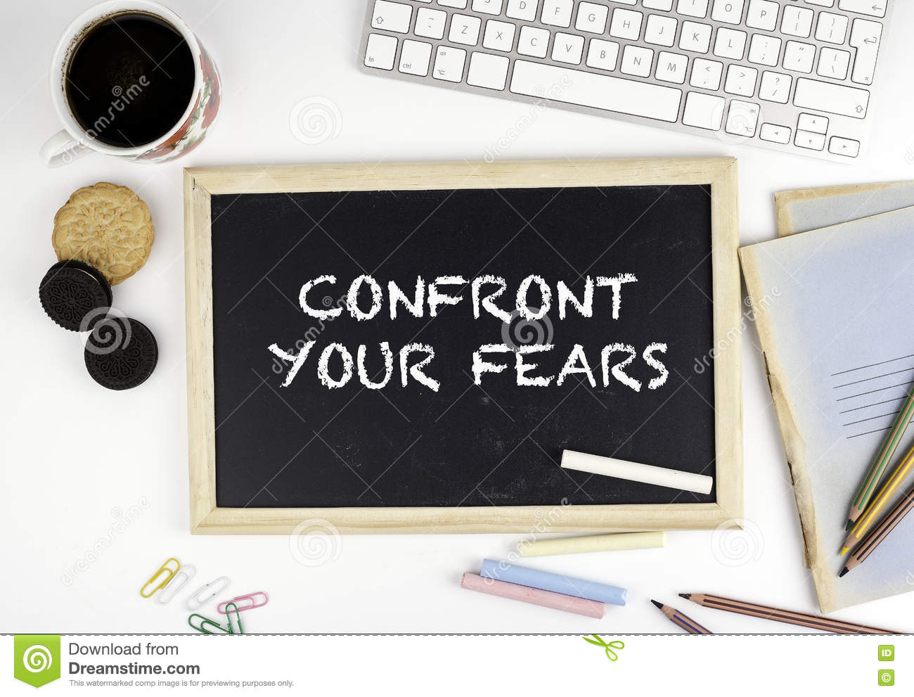 Chalkboard on office desk with text: Confront Your Fears