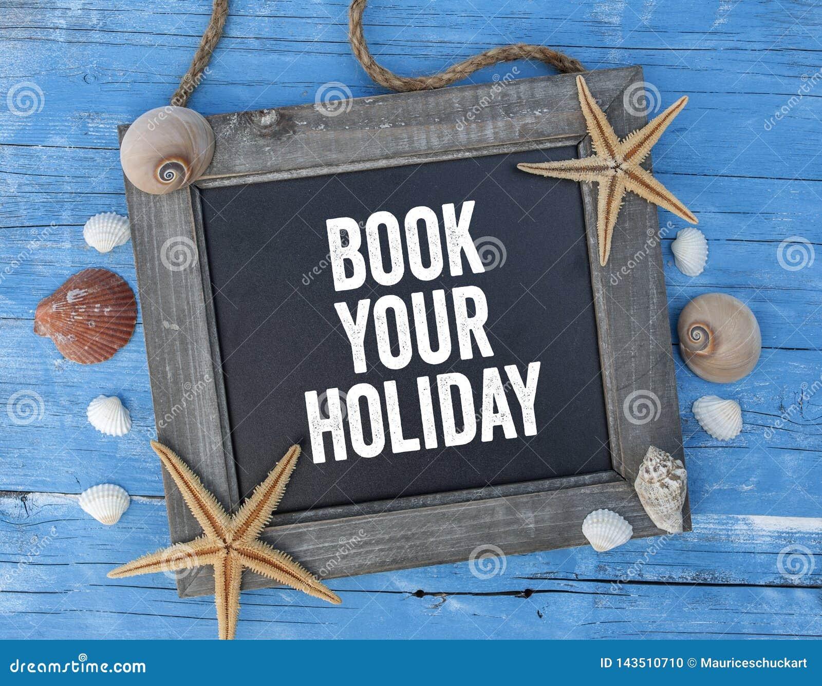 Chalkboard z morską dekoracją na błękitnym drewnianym tle z książką twój wakacje