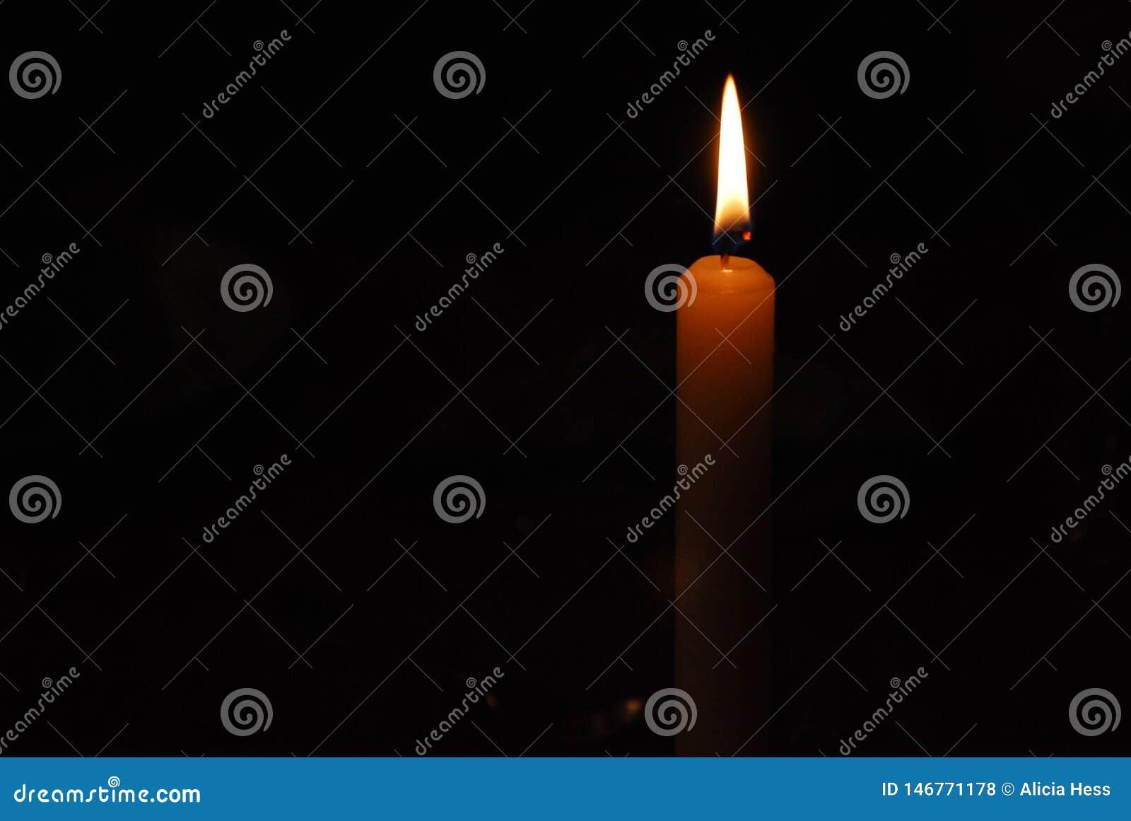 A chama de uma luz da vela na escuridão