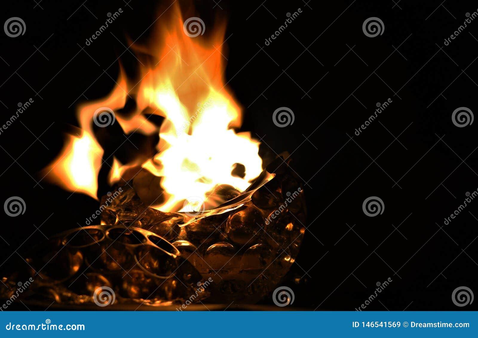 Chama do fogo de vela de vidro quebrada do formulário na escuridão