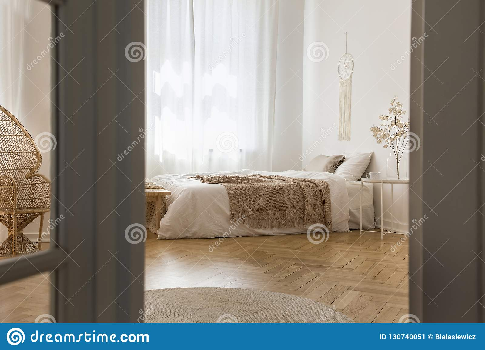 Chambre à coucher élégante blanche conçue avec les matériaux naturels