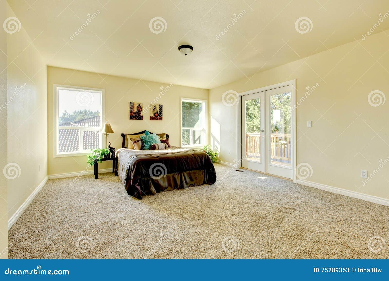 Chambre à coucher élégante et simple dans des tons laiteux avec le tapis beige