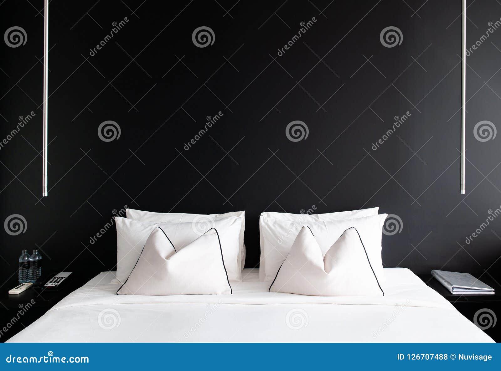 Chambre à coucher avec le lit blanc de mur noir, oreillers table latérale moderne, La