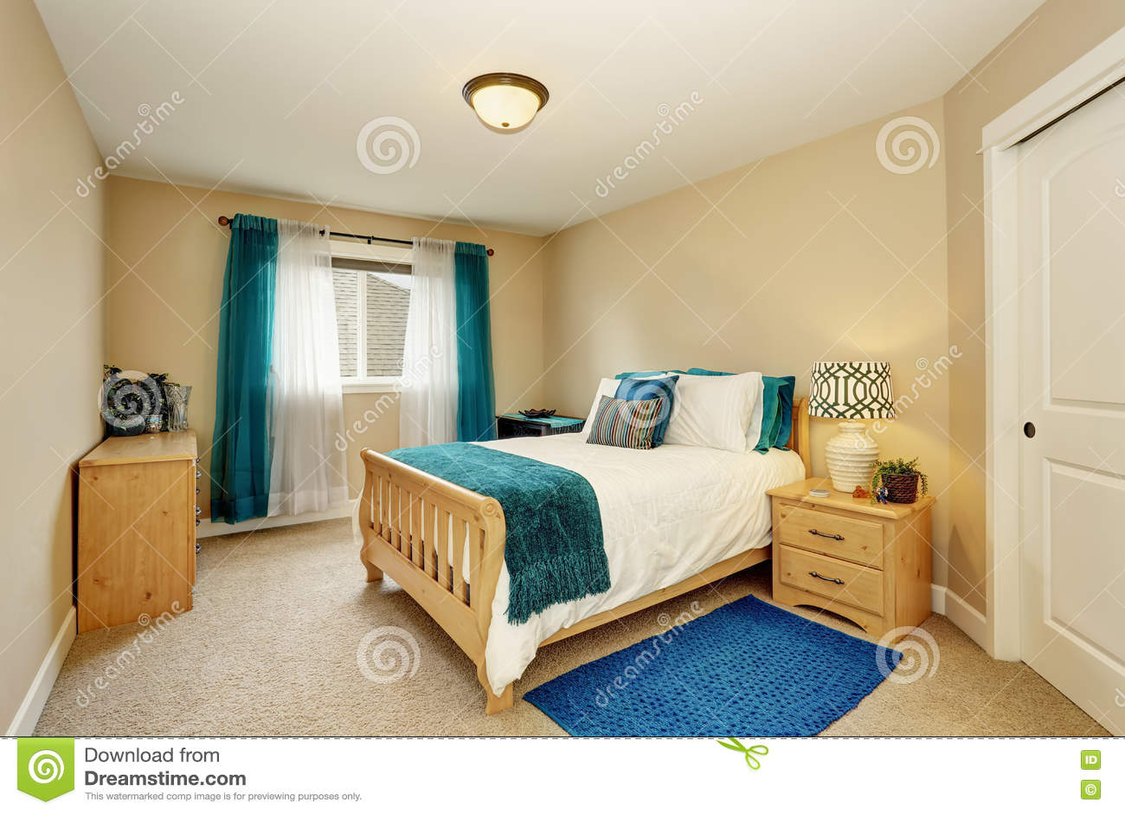 chambre coucher beige ordonn e avec le rideau en turquoise et le lit en bois photo stock. Black Bedroom Furniture Sets. Home Design Ideas