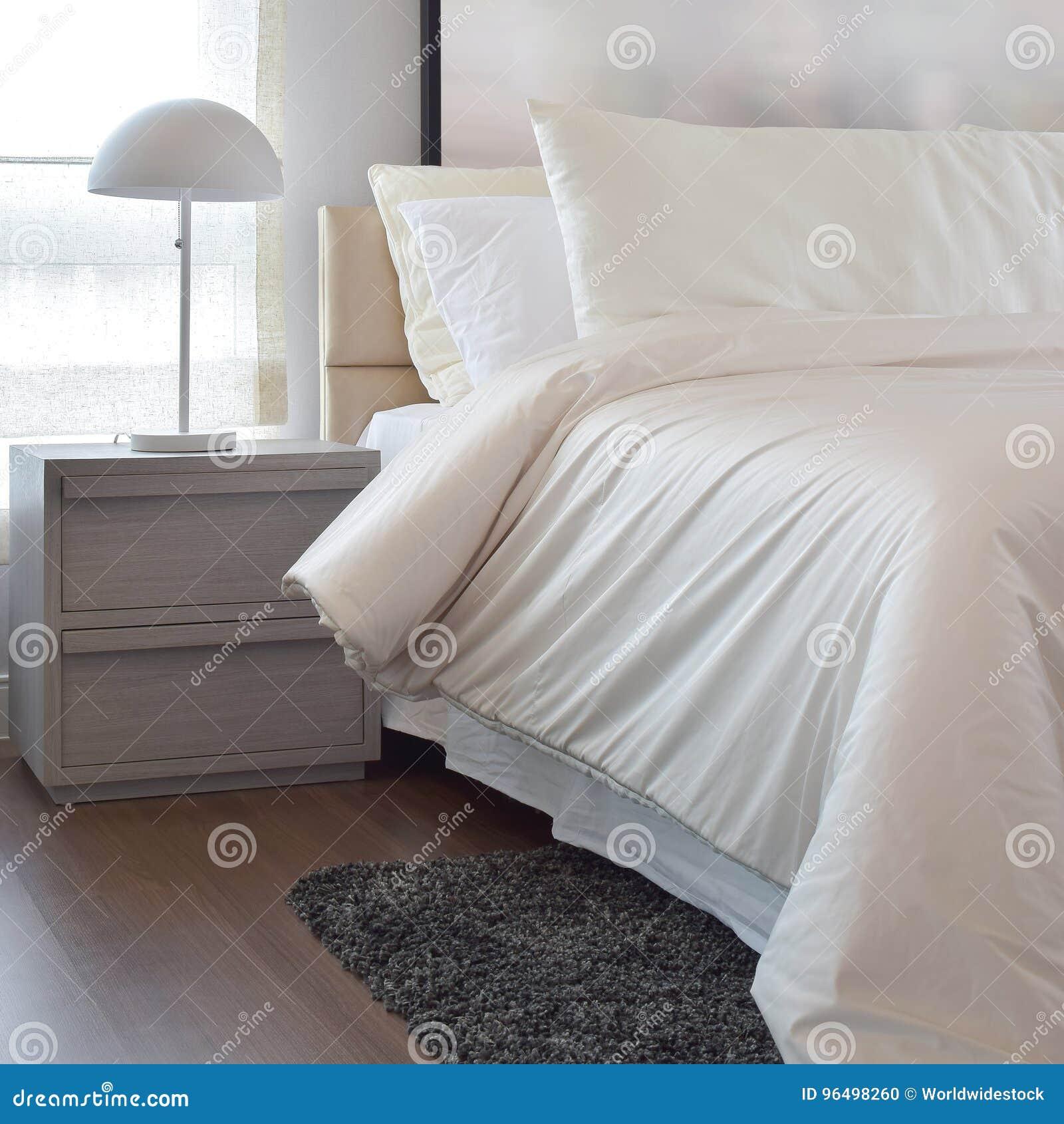 Chambre à coucher confortable avec les oreillers et la lampe de lecture sur le chevet t