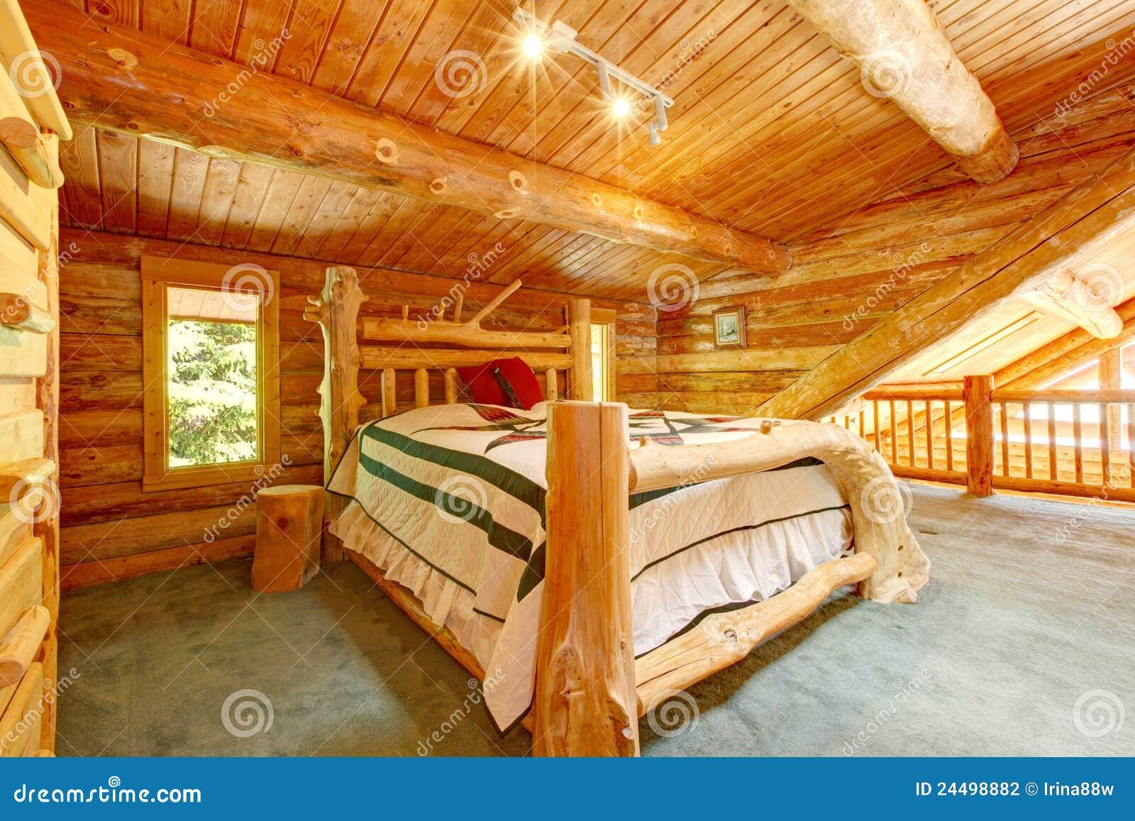 Chambre à coucher de cabine de log sous le grand plafond en bois.