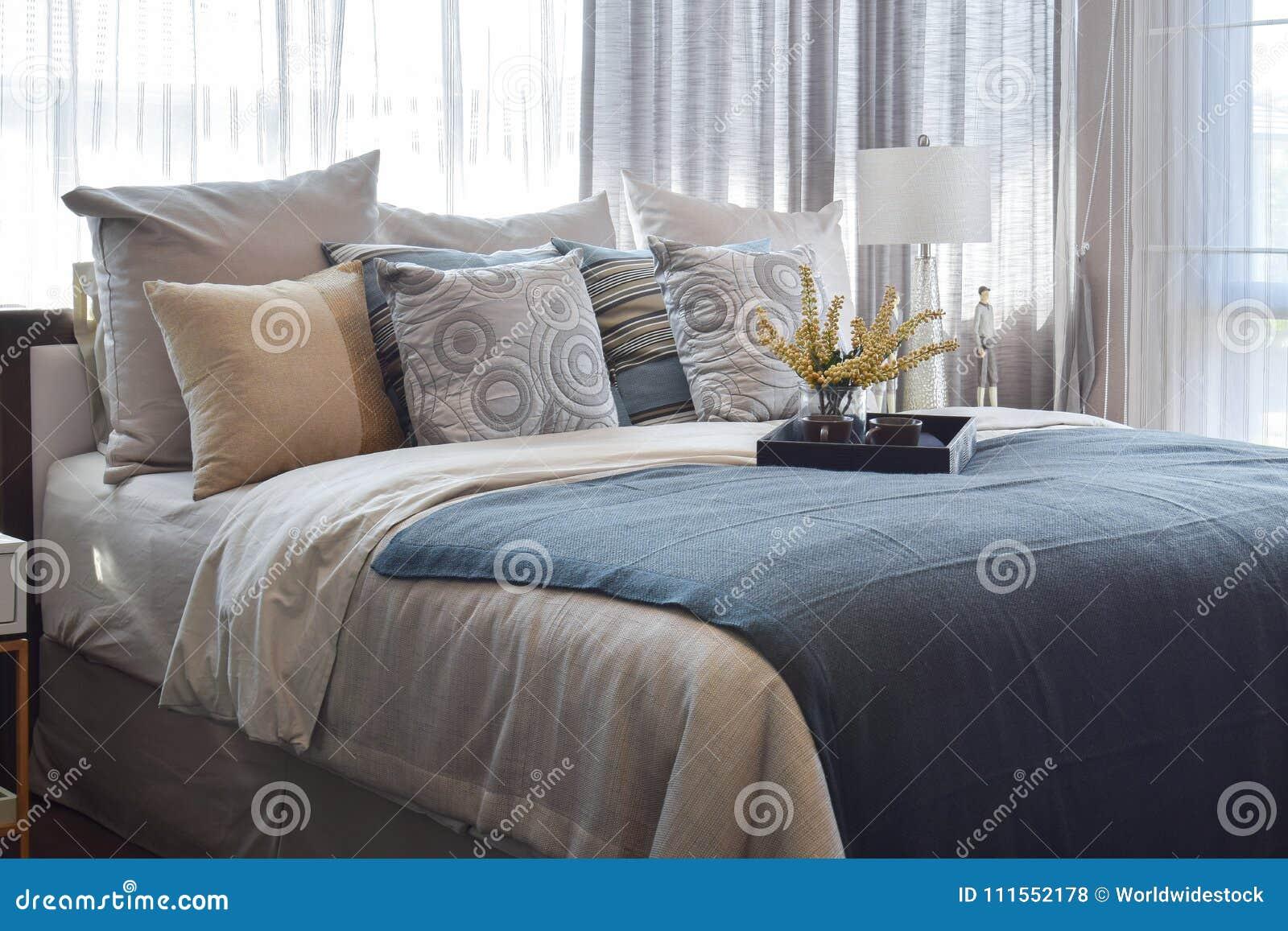Chambre à coucher de luxe avec les oreillers rayés et service à thé décoratif sur le lit