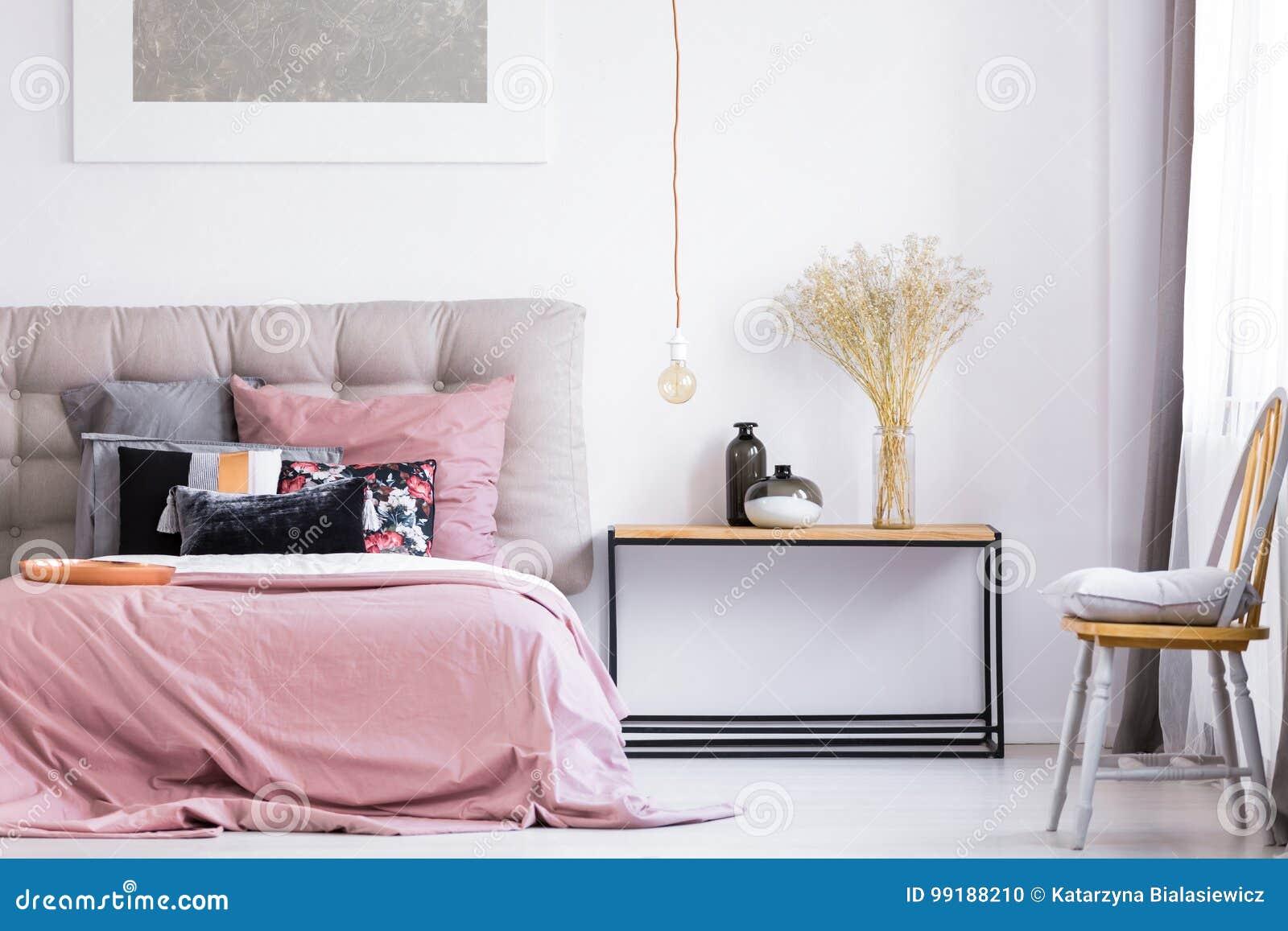 Oreiller Gris Sur La Chaise Orange Sous La Fenêtre Dans La Chambre à Coucher  Moderne Avec La Literie Rose Sur Le Lit Grand