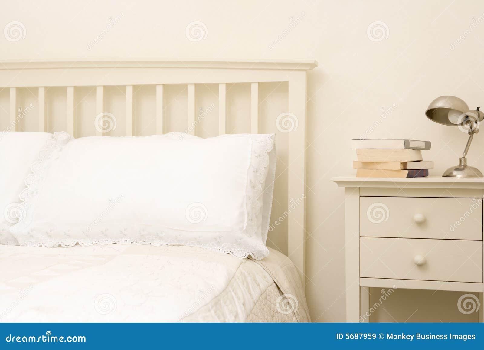 Chambre à coucher vide avec des livres sur le nightstand