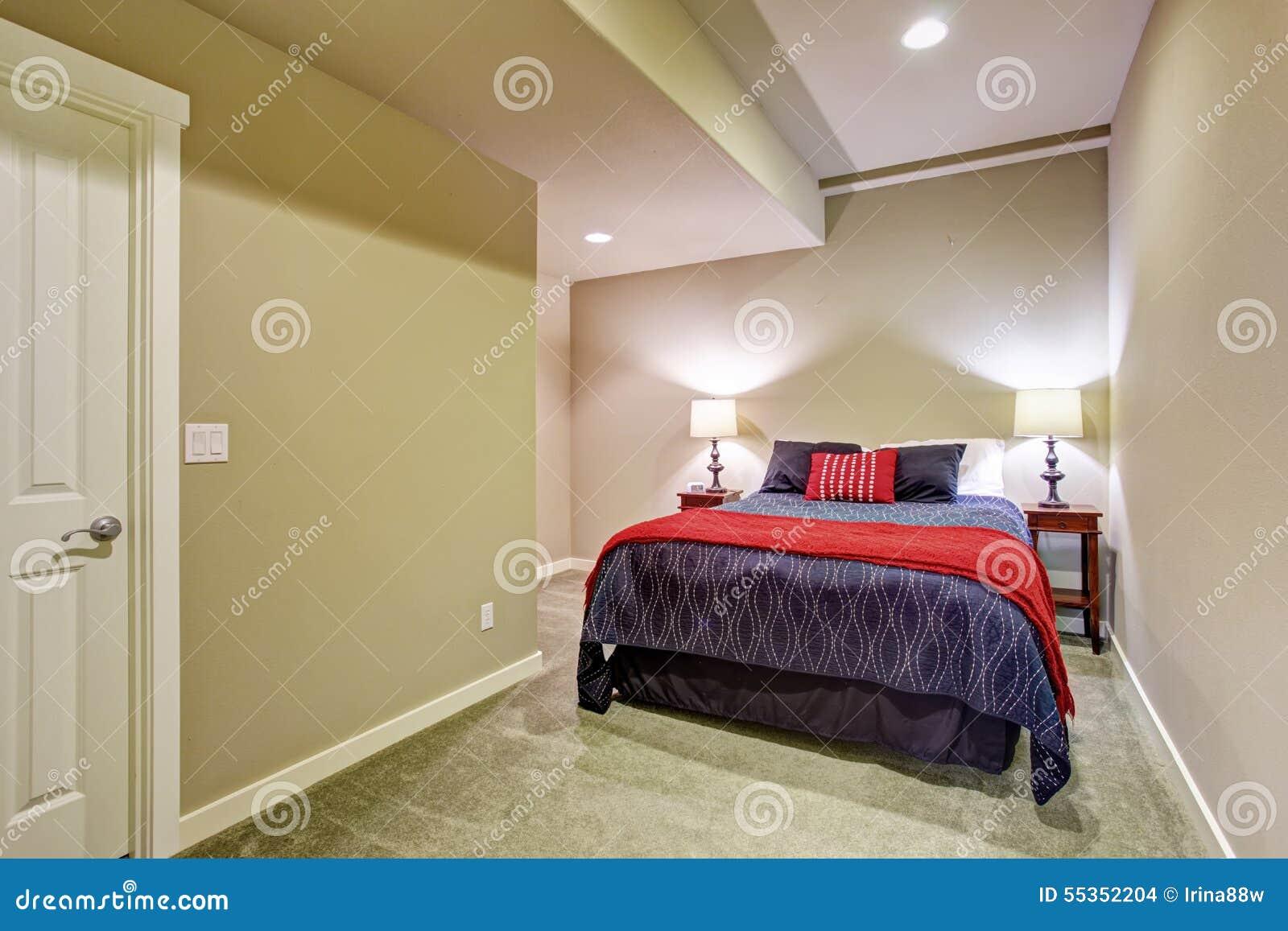 Chambre à coucher d'invité de sous sol avec le lit bleu et rouge ...