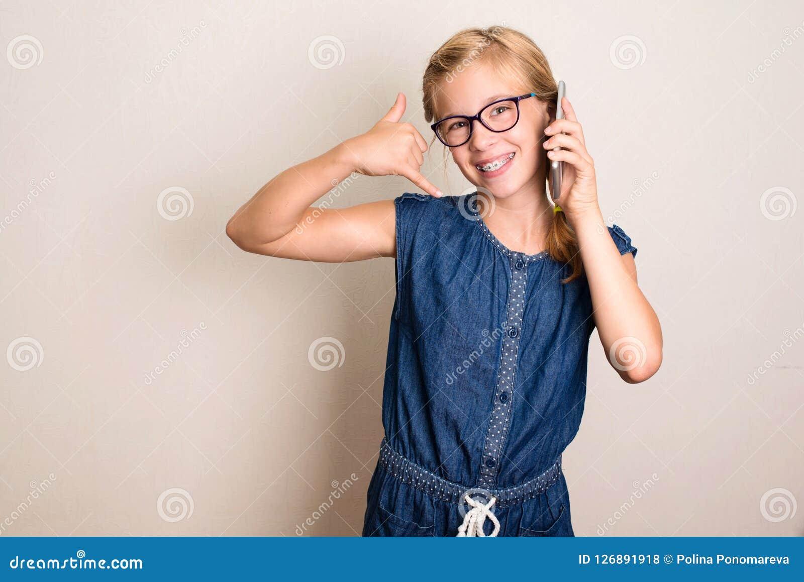 Chame-me para trás Menina adolescente bonita com o smartphone que mostra a uma chamada me