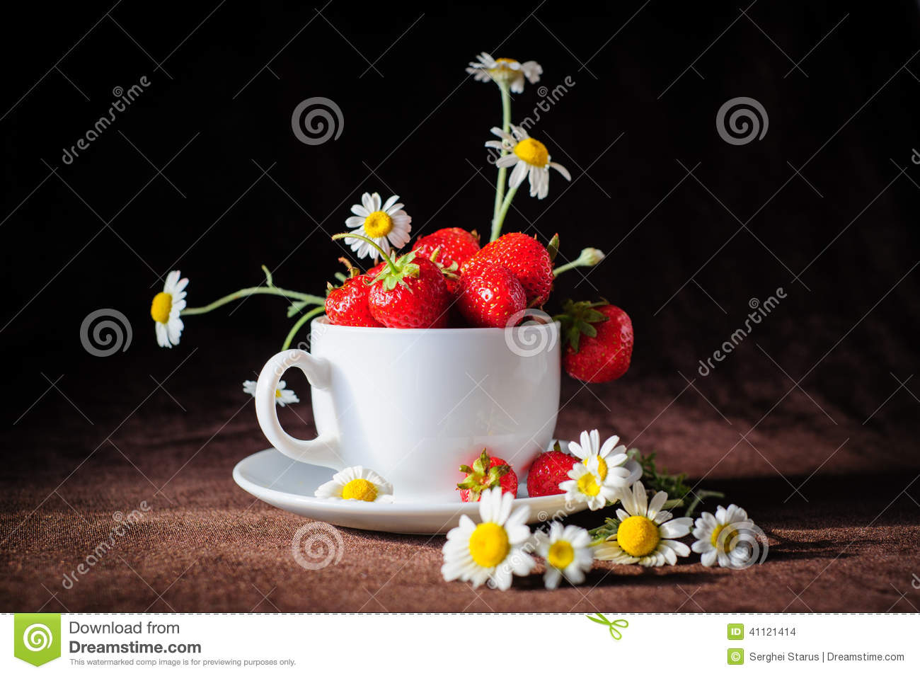 Chamomiles and strawberries in the cup