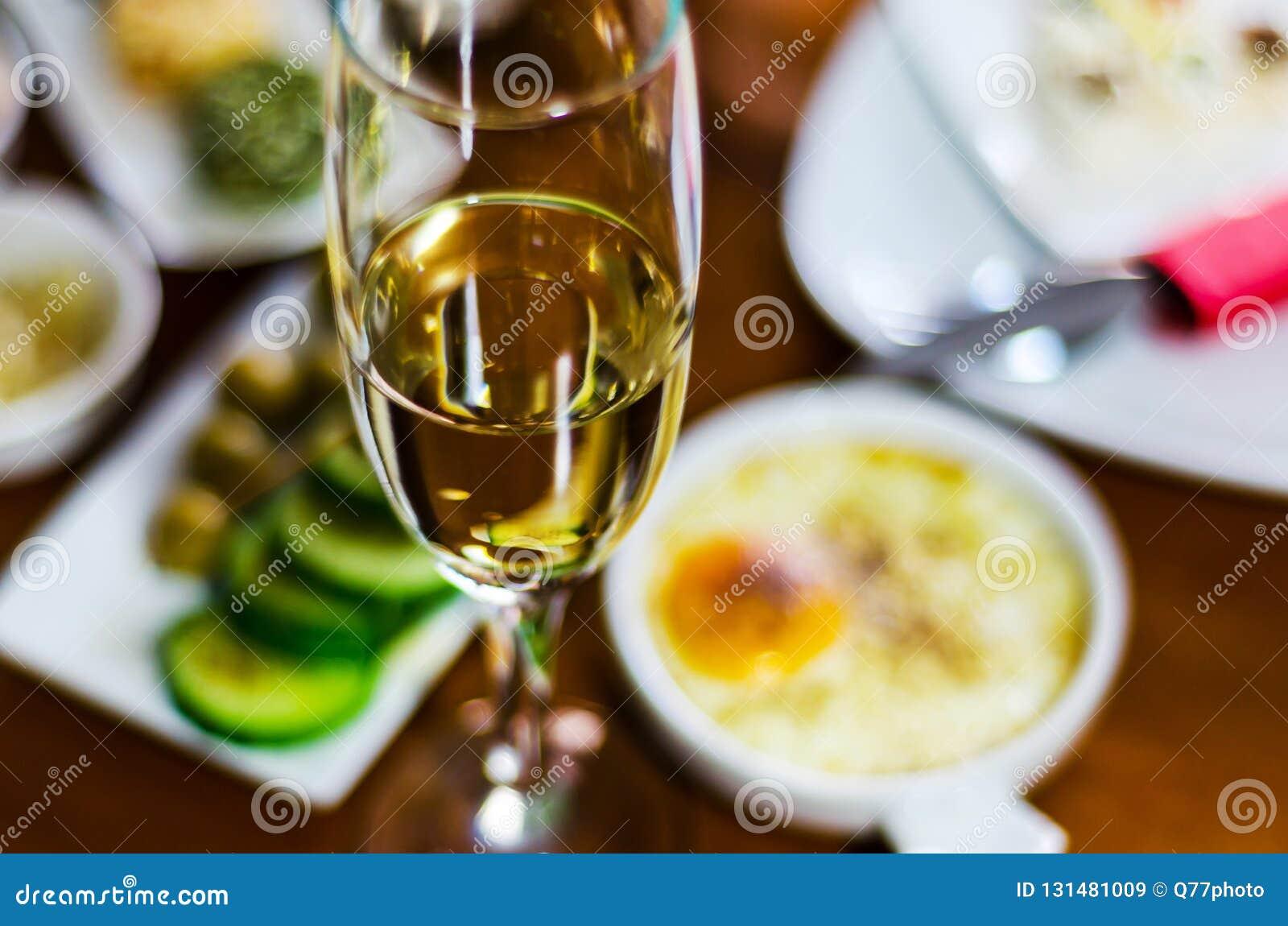 Champán con los aperitivos determinados en los pequeños bocados de las porciones, sanos y deliciosos, sistema sabroso