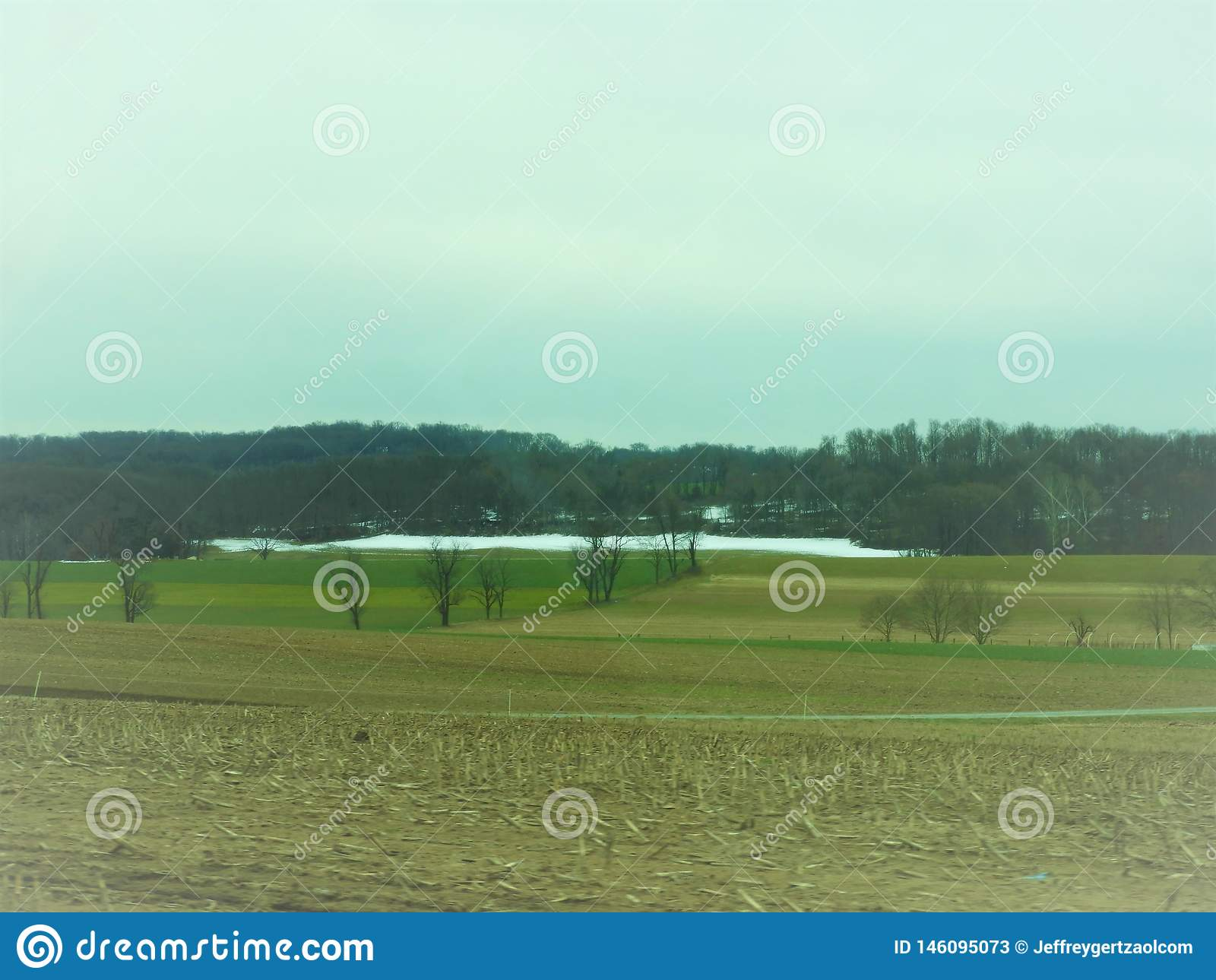Champ accidenté en Pennsylvanie avec la neige et arbres dans la distance