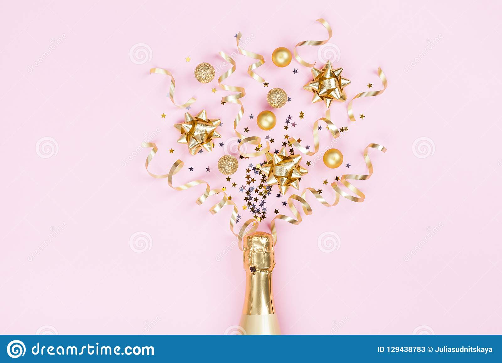 Champagne bottle with christmas decoration from confetti stars, golden balls and party streamers on pink background. Flat lay.